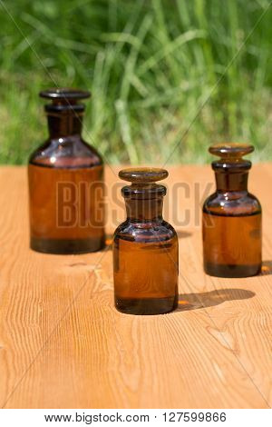 little brown bottles on wooden board and grass
