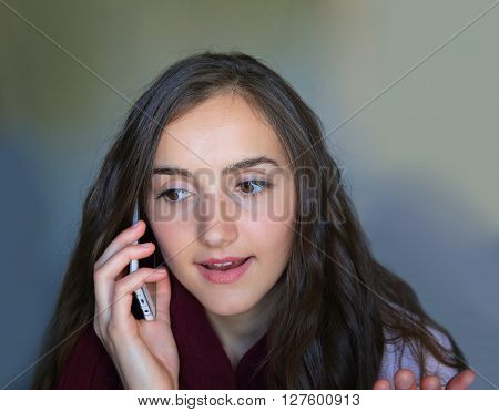 Girl with a mobile phone speaking on the grey background.