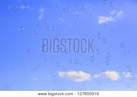 Delicate soap bubbles floating in a blue sky