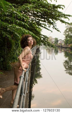 Young asian woman stands on the embankment of the river.