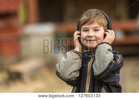 Little boy listening to music on headphones in the street, closeup portrait.