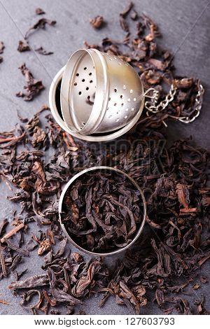 Tea Strainer Full Of Dry Tea Leaves On Slate Stone