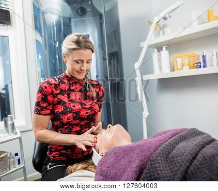 Beautician Giving Face Massage To Woman In Parlor