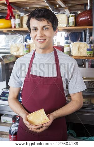 Confident Salesman Holding Cheese Cube At Grocery Store