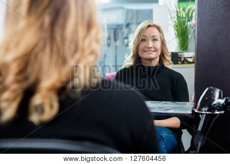 Reflection Of Female Customer Smiling In Salon