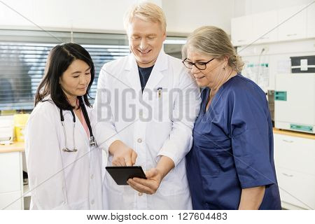 Doctor Using Digital Tablet With Team In Clinic