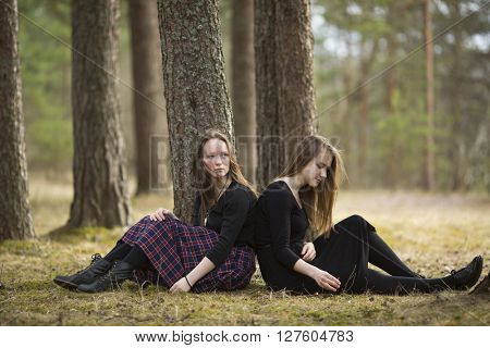 Teenagers girls pensively sitting on the ground in the forest.