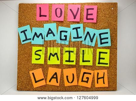 Love, Imagine, Smile, Laugh. Inspirational words. The concept of how life should be lived. A cork board with inspirational words written with sticky notes.
