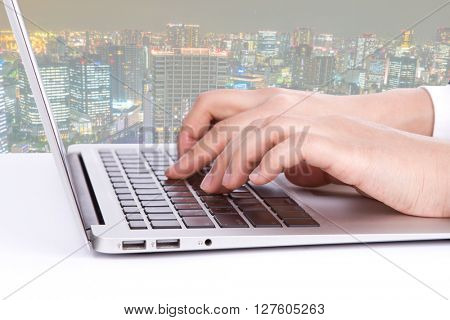 Closeup of business woman hand typing on laptop keyboard with cityscape