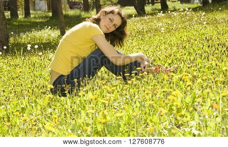 Young European woman brown hair sit on meadow with yellow dandelions.