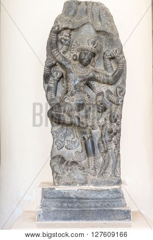 Thanjavur India - October 14 2013: Cholas era statue of the dancing Lord Shiva at the Thanjavur Palace. Hard granite placed against white wall. This pose of Shiva is called Nataraja. Parts of his body have been blackened by numerous caresses.