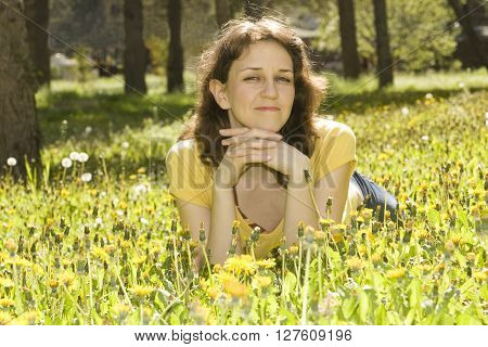 Young European woman with brown hair lay on meadow with yellow dandelions