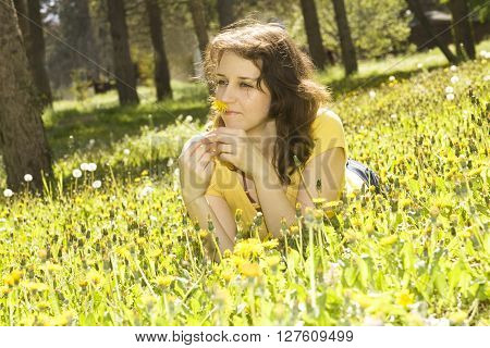 Young European woman withbrown hair lay on meadow with yellow dandelions.