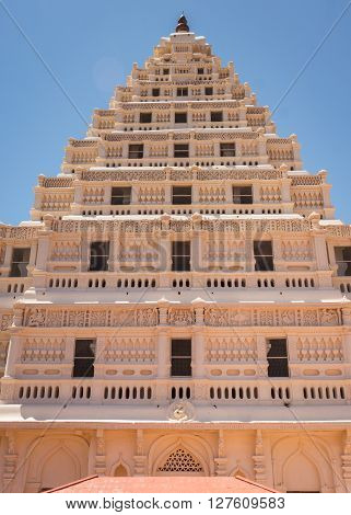 Thanjavur India - October 14 2013: The front of the beige Arsenal Tower at Thanjavur Palace against a blue sky. Focus on one facade of this pyramid. Lakshmi and other decorations worked in frescos.