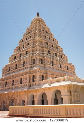Thanjavur India - October 14 2013: The beige Arsenal Tower at Thanjavur Palace against a blue sky. Corner shot shows front and side. Lakshmi and other decorations worked in frescos.