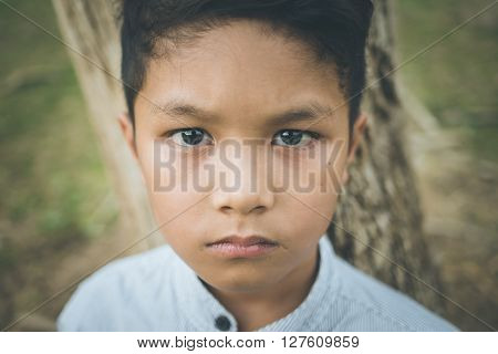 scared and alone, young  Asian child who is at high risk of being bullied, trafficked and abused, selective focus