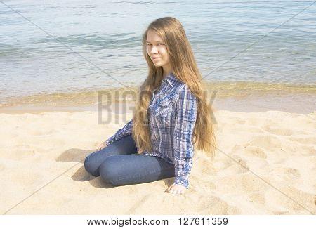 Young beautiful girl European long brown hair sits on sandy beach near sea.