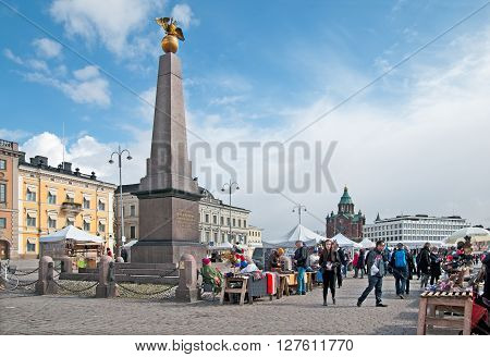 HELSINKI, FINLAND - APRIL 23, 2016: People on The Market Square near souvenir shops. On the left is The Tsarinas Stone Obelisk. On the background is The Uspenski Cathedral.