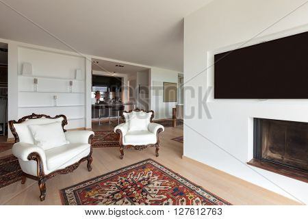 Interiors of new apartment, wide living room with white armchairs