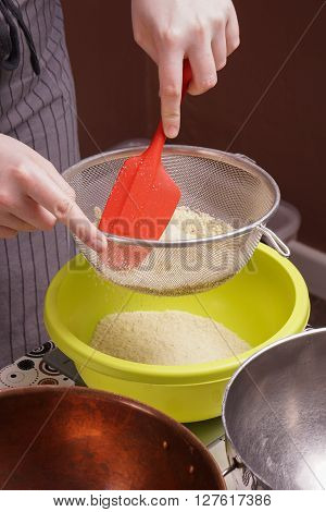 hands sifts flour in to a bowl for cake baking