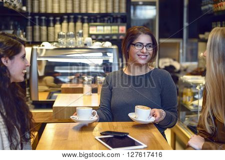 Smiling waitress serving coffee to two young women seated at a table in a bistro or restaurant