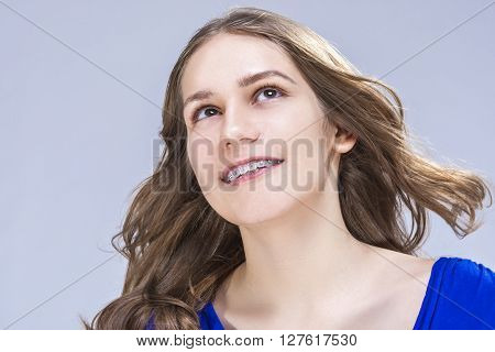 Caucasian Female Teenage Girl With Teeth Brackets in Studio. Sitting and Smiling. Horizontal Image Composition