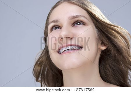 Closeup Portrait of Caucasian Female Teenage Girl With Teeth Brackets. Posing in Studio. Horizontal Image Composition