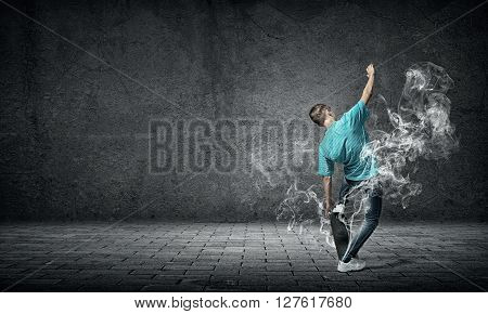 Young guy riding skateboard and smoke from under wheels