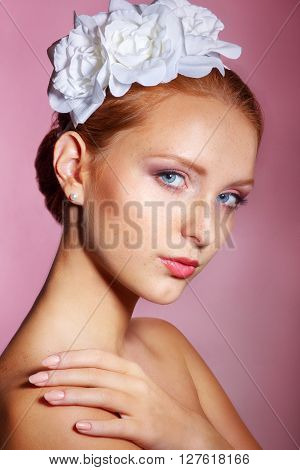 Bridal Beauty .Beautiful young woman with professional make up ..Bride's portrait on a pink background.Youth and Skin Care Concept.Girl with red hair