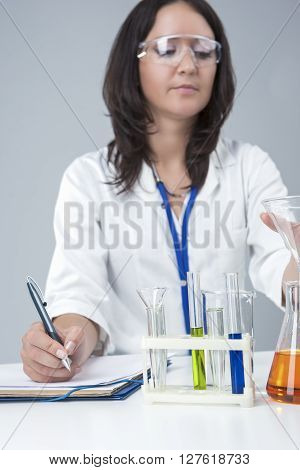 Female Caucasian Laboratory Staff Researching Liquids in Lab Glassware. Jotting Down the Results. Vertical Image Composition