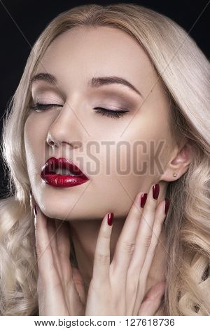Beauty Woman with Perfect Makeup. Beautiful Professional Holiday Make-up. Red Lips and Nails. Beauty Girl's Face isolated on Black background. Glamorous Woman. Blonde woman with perfect curly hair