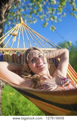 Portrait of Smiling Caucasian Blond Lady Resting in Hummock During Spring Time Outdoors.Vertical Shot