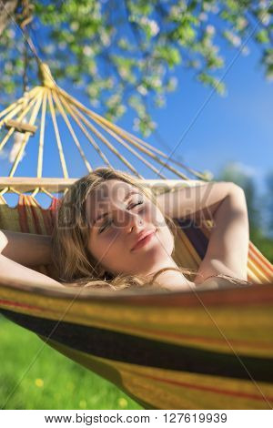 Cute Relaxing Caucasian Lady Resting in Hummock and Dreaming Outdoors.Vertical Shot