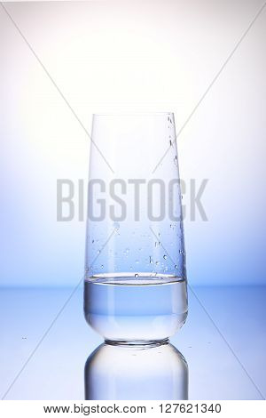 One-third Full Drinking Glass With Reflection In Drops Of Water