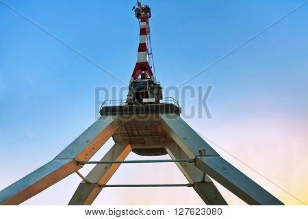 Cargo crane in the port on sunset sky background