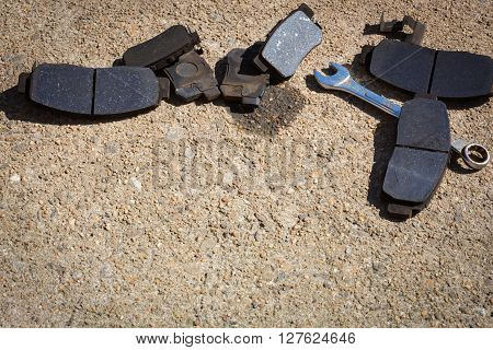 Worn used Brake Pads with tools on concrete