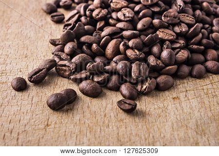 Black coffee beans spiled on wood background