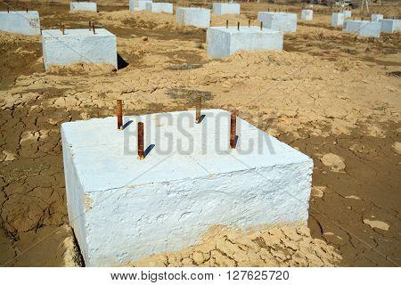 Concrete Foundation Construction Area. Concrete blocks on a wet sand ground.