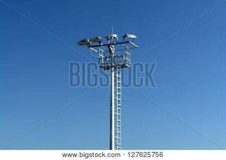 Electric Light Pole on the Blue Sky.