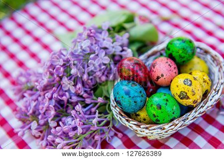 painted Easter quail eggs in a basket. Painted quail eggs at basket