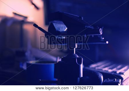 Vise on table in dark room, toned colorized image, side view, backlit