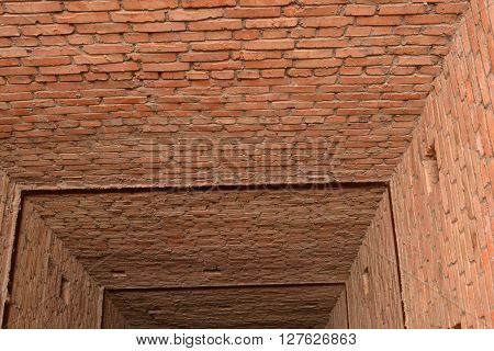 Red brick tunnel with rectangular walls and small holes in the walls.