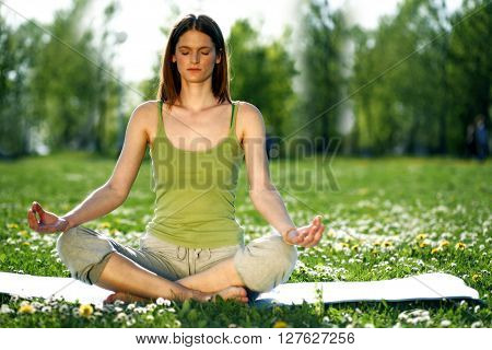 Young women practise yoga by day in nature