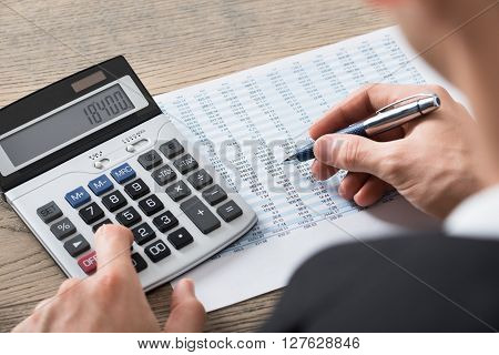 Businessman Analyzing Accounting Document With Calculator