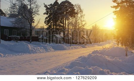 Russian village landscape. Road in the snow during a stunning sunset.