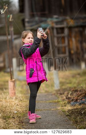 Little girl standing on the street taking a selfie on a smartphone.
