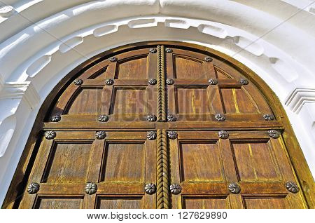 Architecture elements. Old wooden door with metal rivets and arch of white stone - architecture background