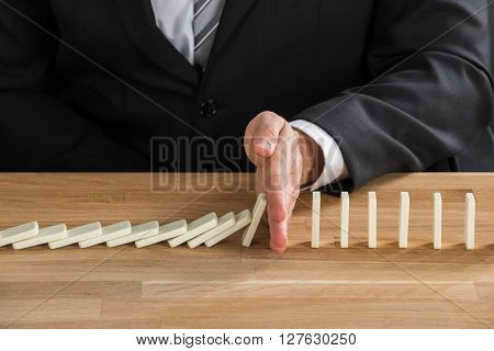 Businessman Stopping Dominoes From Falling