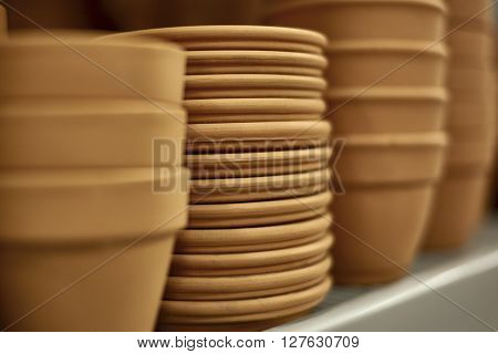 Rows of Clay Pots with Trays on Shelf with shallow depth of field