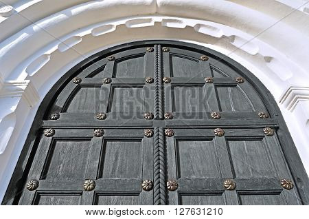 Architecture detailed background - aged wooden grey door with iron rivets and upper arch of white stone - vintage architecture background
